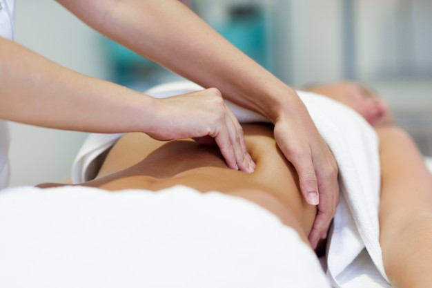 woman-having-abdomen-massage-by-professional-osteopathy-therapist_1139-1123